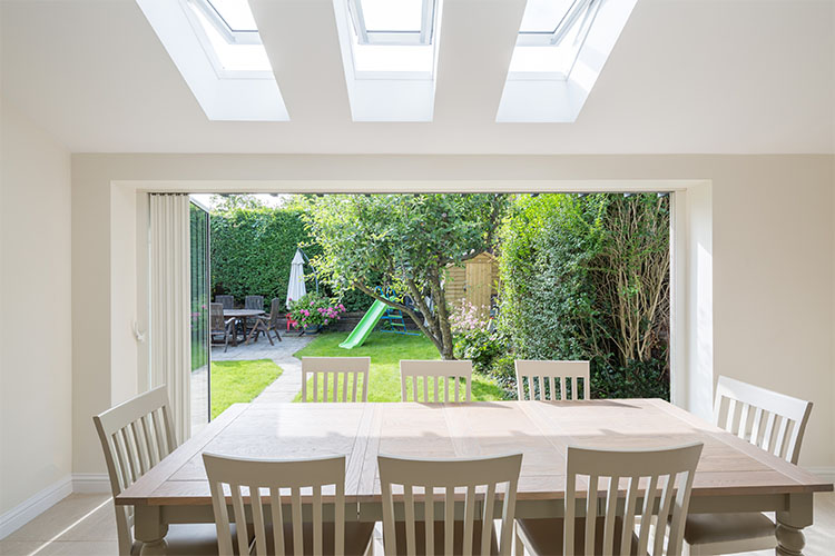 View to garden through full width bi-folds from kitchen table in a 1920s semi-detached house with modern extension and loft conversion by Space Program Architects