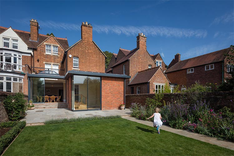 View from garden with little girl running towards a modern house extension by Space Program Architects