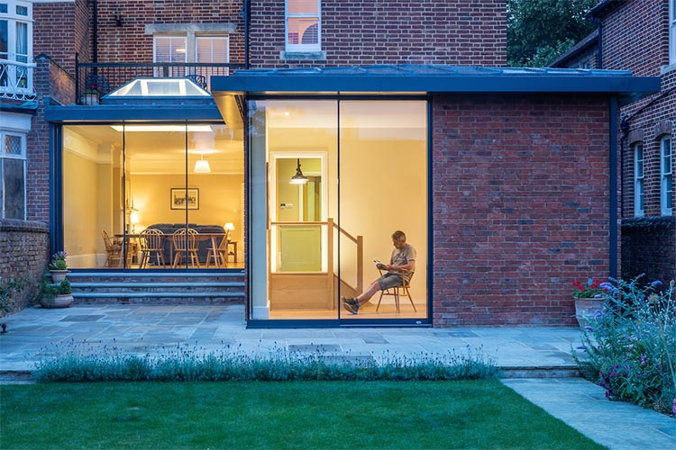 Man sitting reading in garden room of modern house extension by Space Program Architects