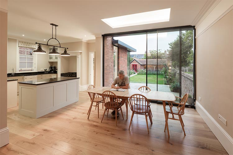 Man sitting at table in open plan kitchen diner in modern house extension by Space Program Architects