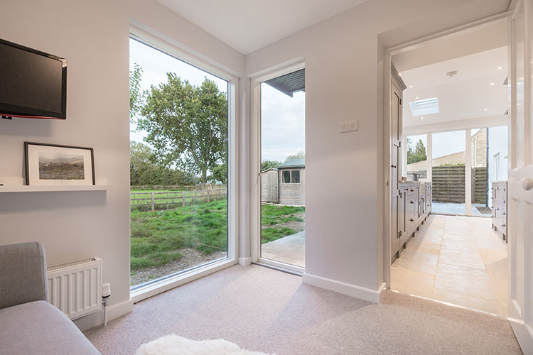 View from snug to open plan kitchen diner and garden in Cotswold House with modern extension by Space Program Architects