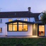 View from garden to open plan kitchen in Cotswold House with modern extension by Space Program Architects