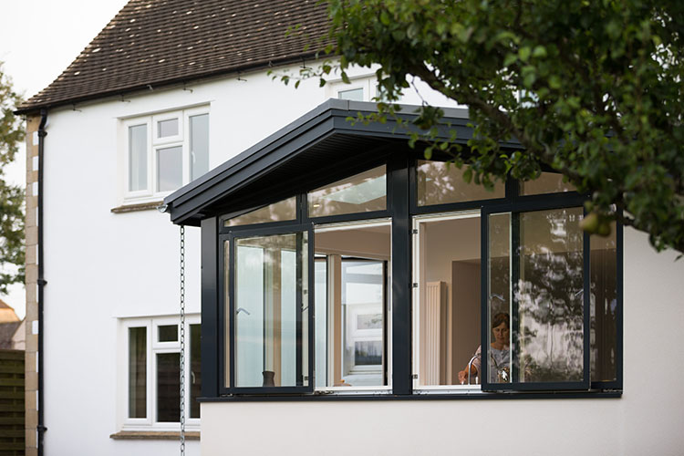 View from garden to open plan kitchen diner in Cotswold House with modern extension by Space Program Architects