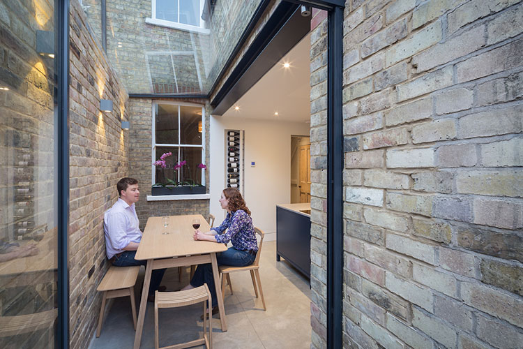 View of couple sitting at kitchen table in modern Victorian terrace side return by Space Program Architects