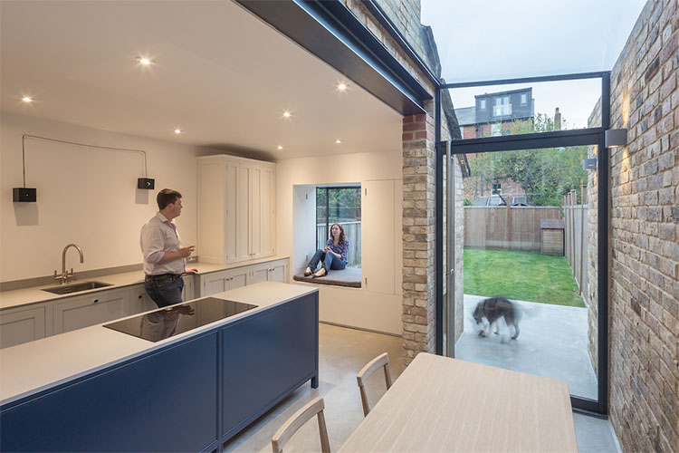 Open plan kitchen diner with women sitting on window seat in modern Victorian terrace side return by Space Program Architects