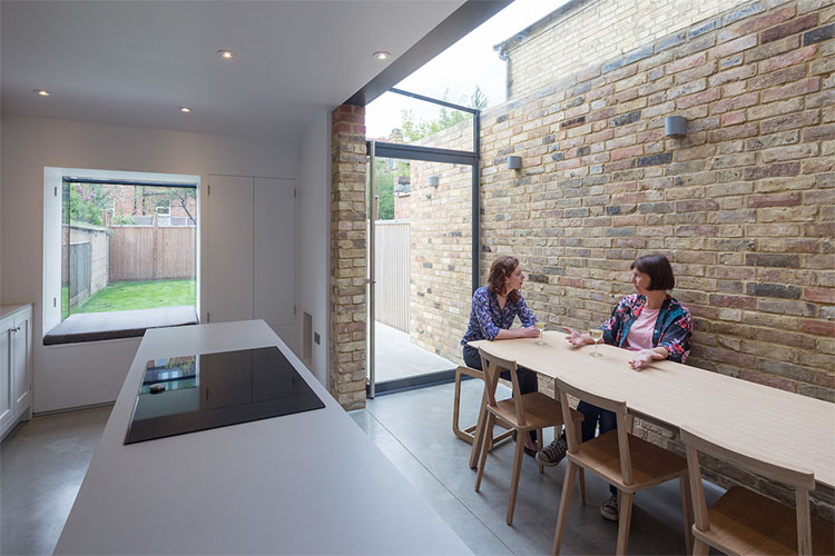 Friends talking at table in kitchen diner of View of couple sitting at kitchen table of modern Victorian terrace side return by Space Program Architects